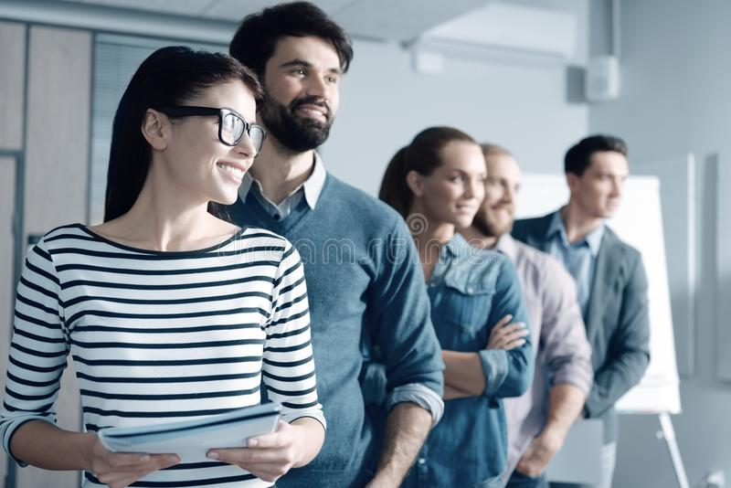 Positive young team standing in the office royalty free stock images