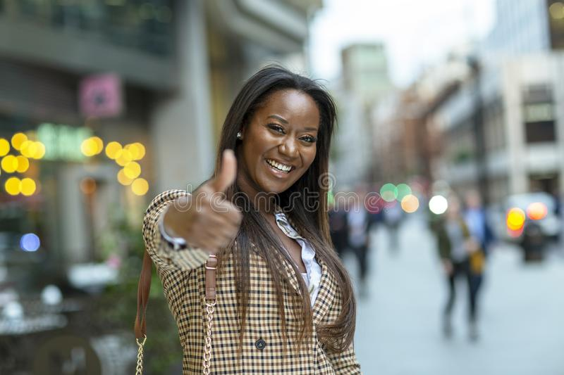 Positive young woman in the city stock photos