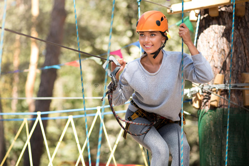 Positive young woman enjoying herself in the high wire park stock images