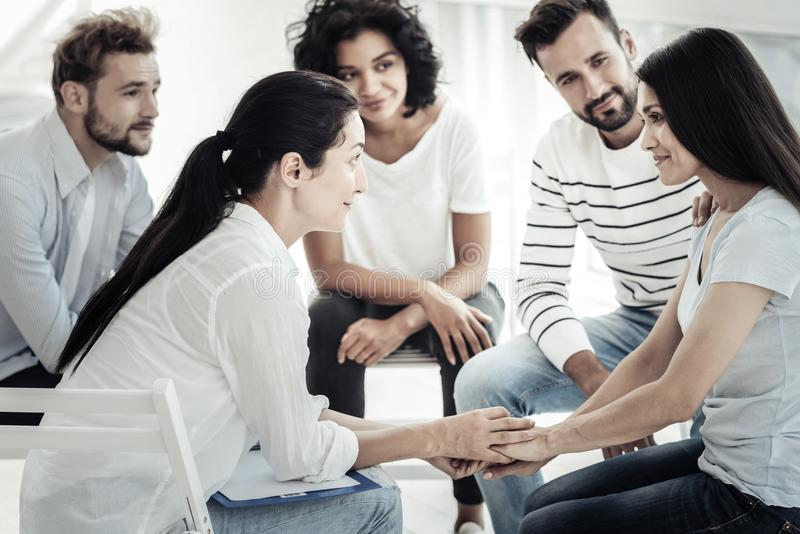 Positive young woman looking at the therapist stock photography