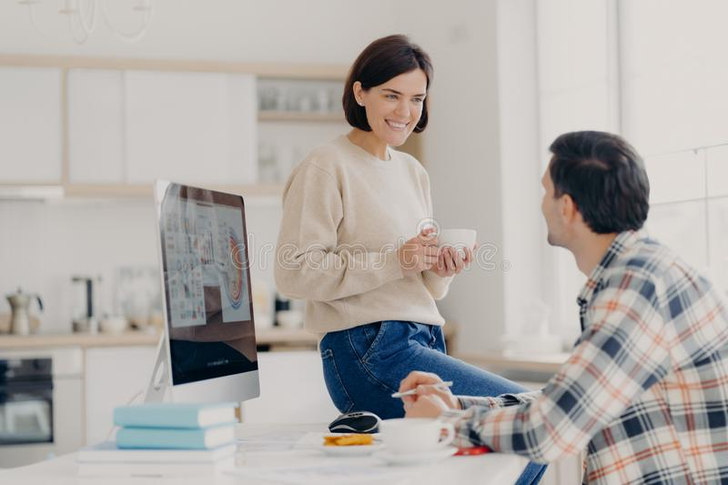 Positive young woman and man discuss renting apartment, pose in coworking space with computer and paper documents, happy wife. Positive young women and men stock image