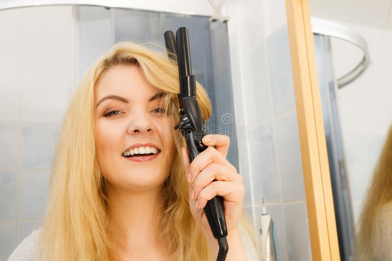 Woman using hair curler. Positive young woman preparing her blonde hair, using curling pin in home bathroom. Hairdo curler creating hairstyle stock photos