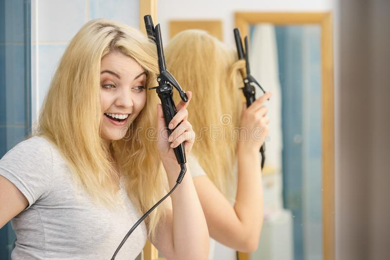 Woman using hair curler. Positive young woman preparing her blonde hair, using curling pin in home bathroom. Hairdo curler creating hairstyle stock photography