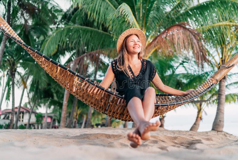 Positive young woman sitting in hammock on the tropical palm beach stock photography