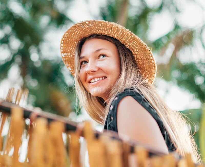 Positive young woman smiling sitting in hammock on the tropical palm beach royalty free stock photography