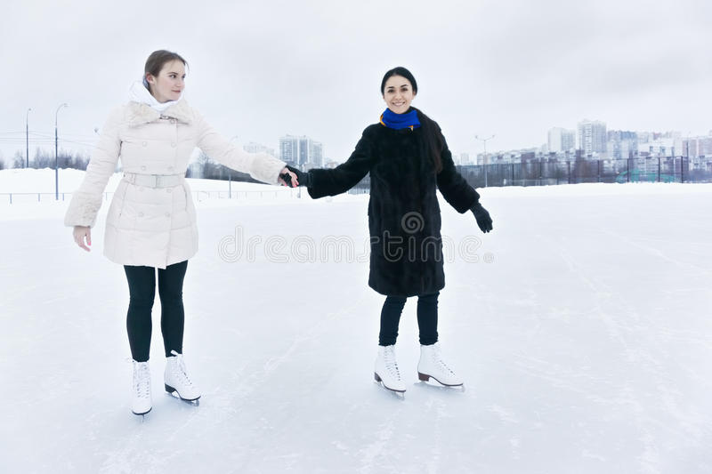 Positive young women on ice rink royalty free stock image