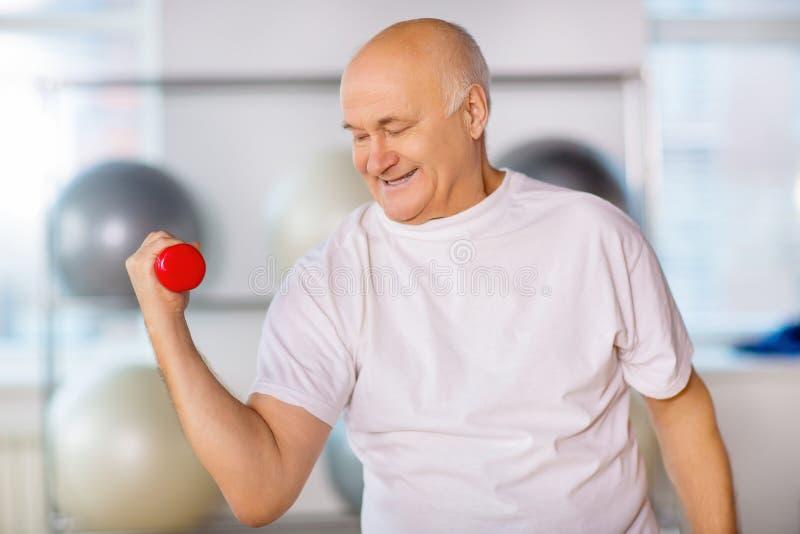Positiver älterer Mann, der mit Gewichten übt lizenzfreies stockbild