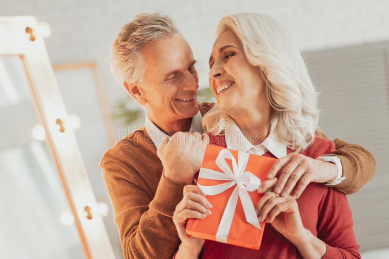 Positiver älterer Mann, der seine frohe Frau umarmt stockbild