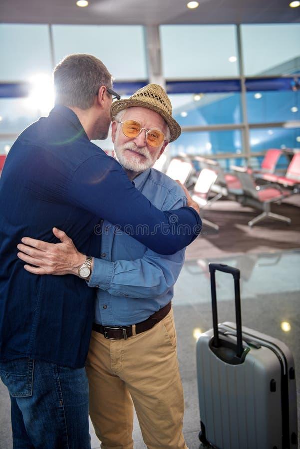 Positiver älterer Mann im Hut umfasst reifen Mann stockfoto