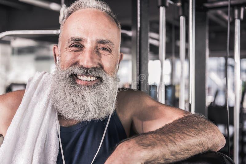Positiver älterer Mann lächelt bei der Stellung in der athletischen Mitte lizenzfreies stockbild