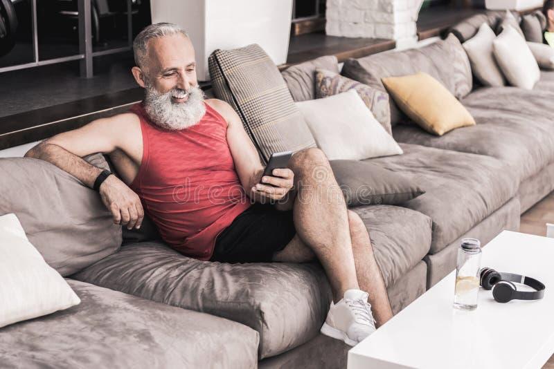 Positiver älterer Mann unter Verwendung des Handys bei der Entspannung in der Turnhalle lizenzfreies stockbild