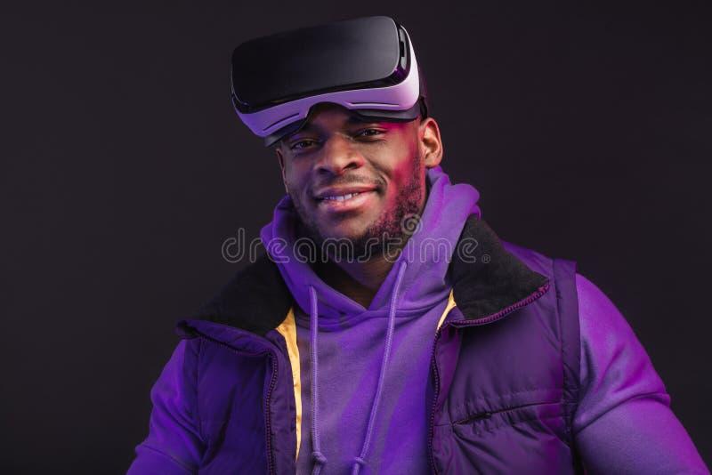 Positiver afrikanischer Mann, der seine VR-Gläser von seinem Kopf auf schwarzem Hintergrund entfernt stockfotografie