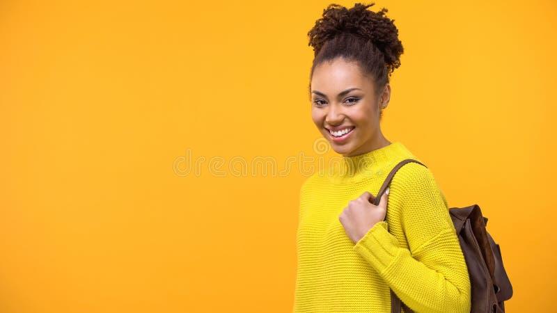 Positiver afrikanischer Student mit lächelnder Kamera des Rucksacks, Hochschulausbildung stockbild