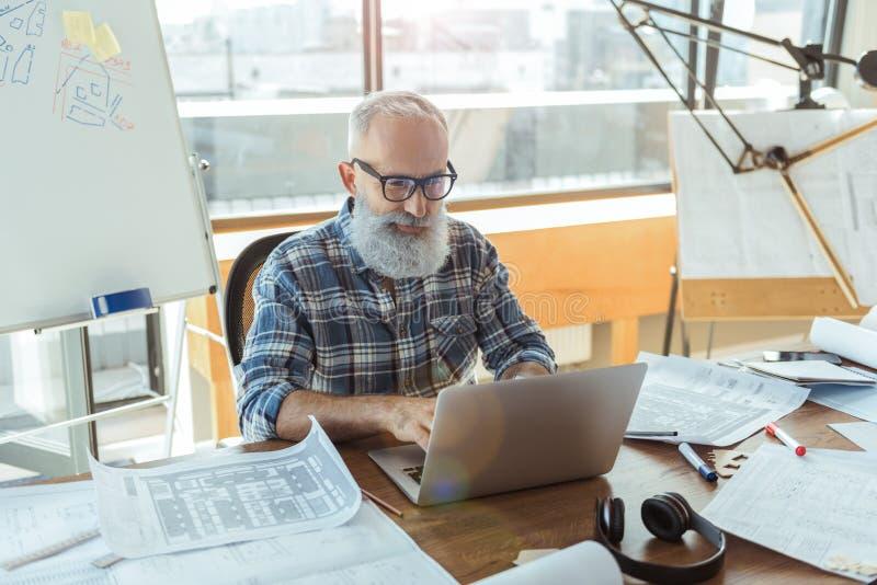 Positiver angenehmer alter Mann arbeitet im Büro lizenzfreie stockfotos