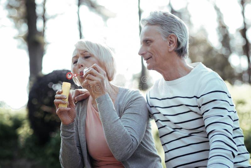 Positiver begeisterter Mann, der seine Frau umfasst lizenzfreie stockbilder