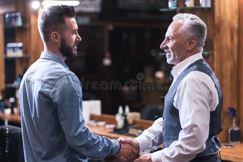Positiver dankbarer Mann, der seine Friseurhand rüttelt lizenzfreies stockbild