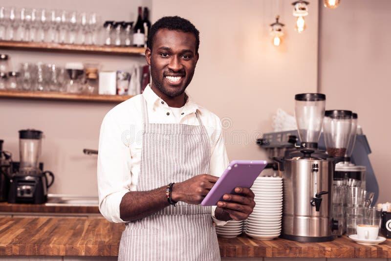 Positiver froher Mann, der eine moderne Tablette hält lizenzfreies stockfoto