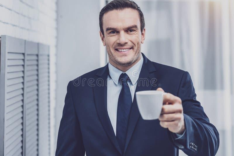 Positiver Geschäftsmann mit Schale Espresso lizenzfreie stockfotos
