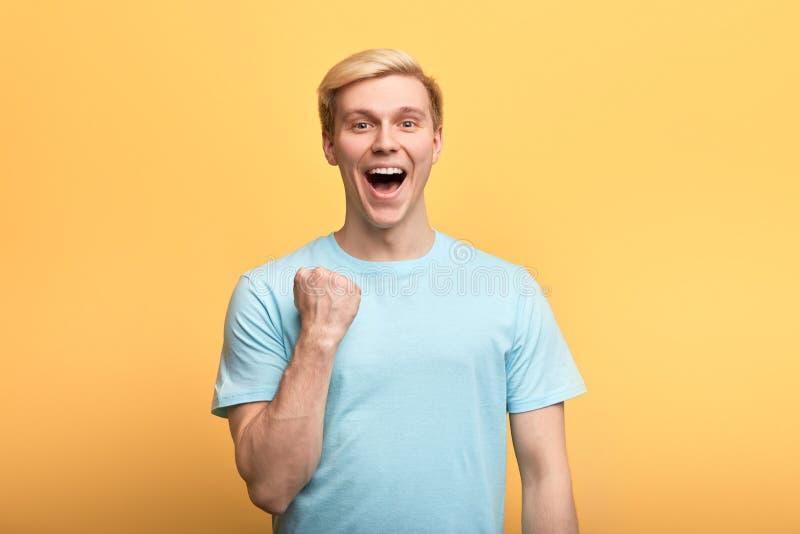 Positiver herrlicher junger emotionaler Mann, der geballte Fäuste hooray in der Geste anhebt stockbilder