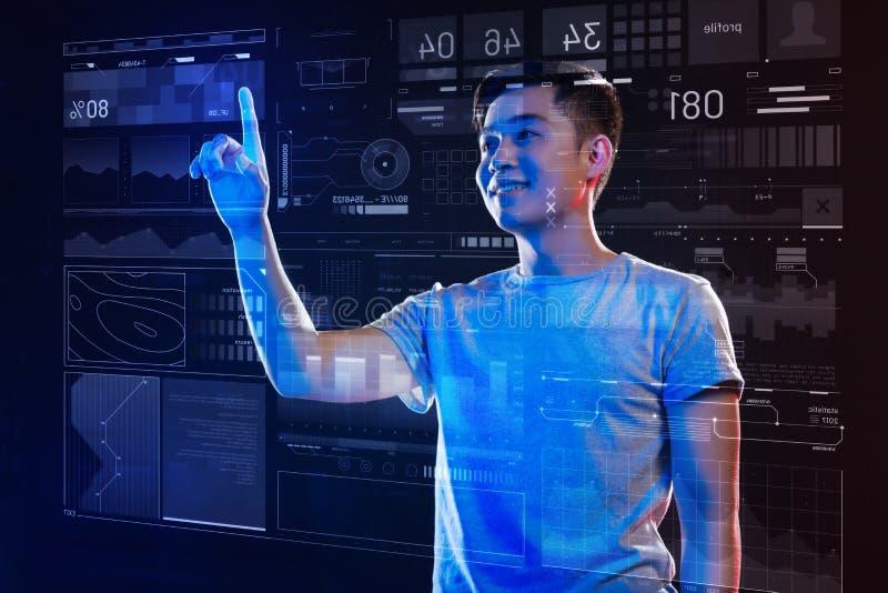 Positiver junger Programmierer, der seine Arbeit lächelt und genießt lizenzfreies stockfoto