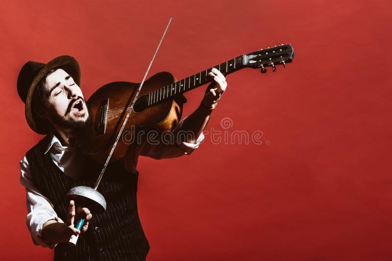 Positiver Kerl im Studio simuliert eine Violine stockfoto