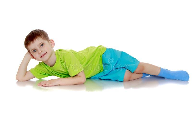 Positiver kleiner Junge, der auf dem Boden liegt lizenzfreie stockfotos
