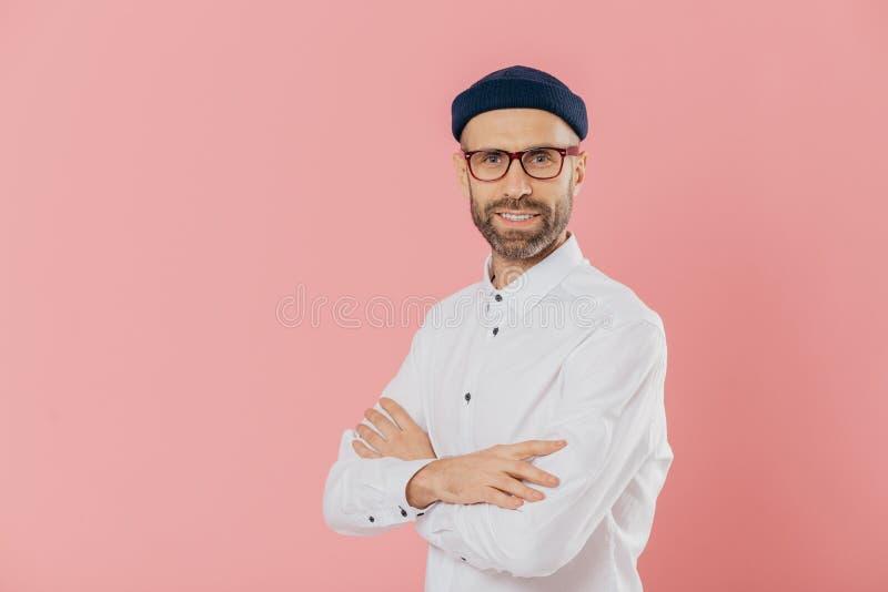 Positiver männlicher Unternehmer mit Selbstüberzeugtem erfülltem Gesichtsausdruck, hält Hände gekreuzt, steht im Profil, schaut d stockbilder