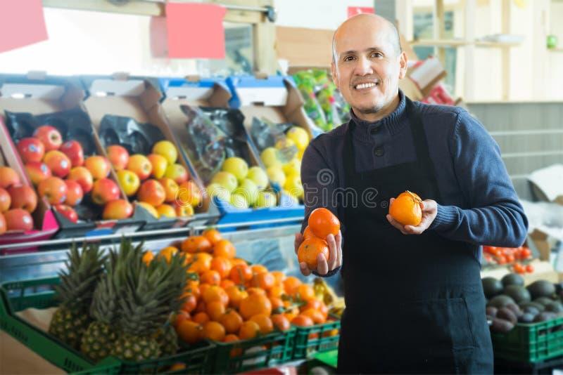 Positiver männlicher Verkäufer bietet Mandarinen an stockbild