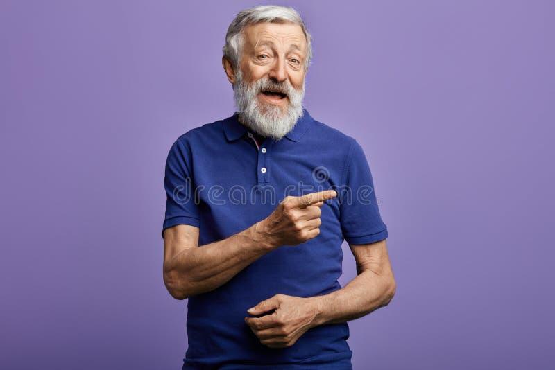 Positiver Mann, der mit der Hand und dem Finger auf die Seite zeigt stockfotografie
