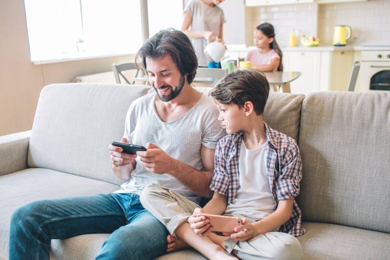 Positiver Mann sitzt auf Sofa und Spielen am Telefon Junge hat dieses Telefon auch, aber er betrachtet diesen seinen Vati hat Mäd lizenzfreies stockbild