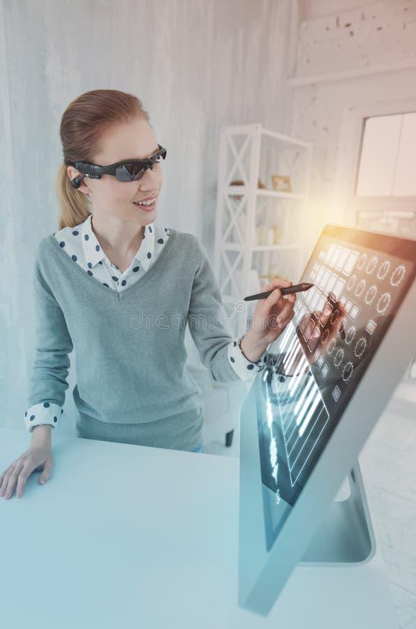 Positiver Programmierer, der mit einem Griffel lächelt und arbeitet stockfotos