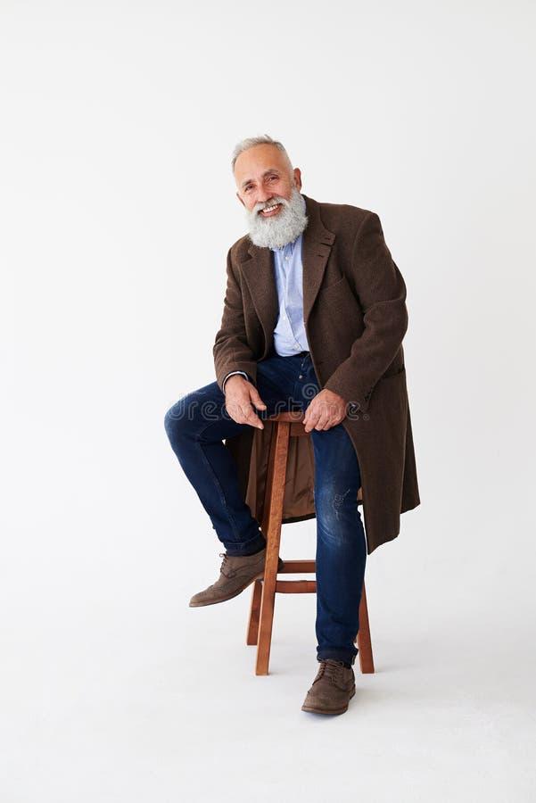Positiver reifer bärtiger Mann im Mantel, der auf Stuhl im Studio sitzt lizenzfreie stockfotos