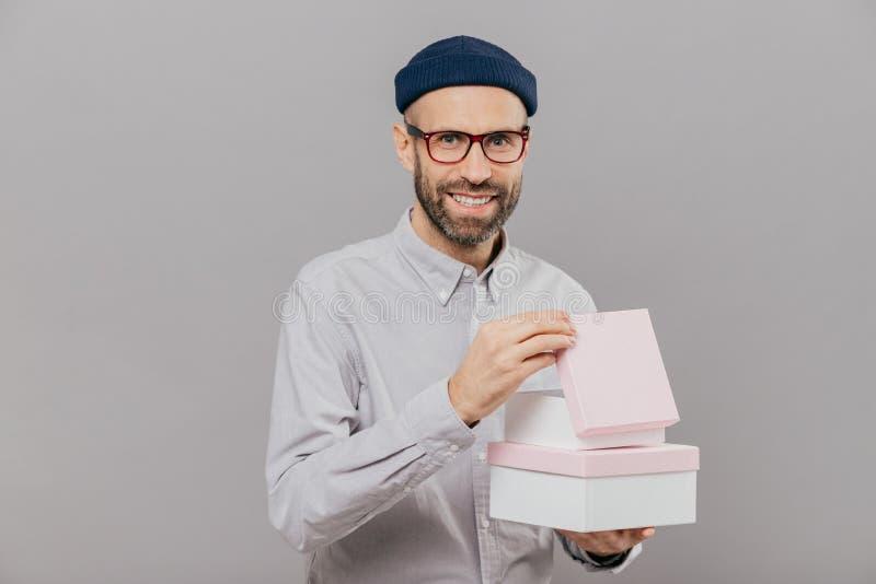 Positiver unrasierter Mann hat Stoppel, trägt Kästen mit Geschenk, öffnet einen von ihnen, hat glücklichen Gesichtsausdruck, träg stockfotos