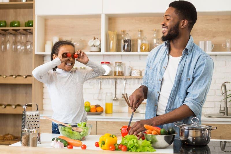 Positiver Vater und Tochter, die Spaß auf Küche hat stockfotografie