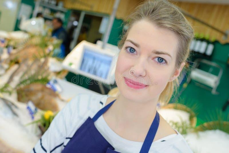 Positiver weiblicher Verkäufer des Porträts, der frische Fische verkauft stockfotografie