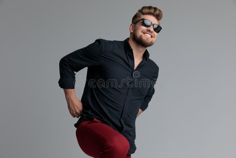 Positiver zufälliger Mann, der seine roten Hosen lacht und zieht stockfotografie
