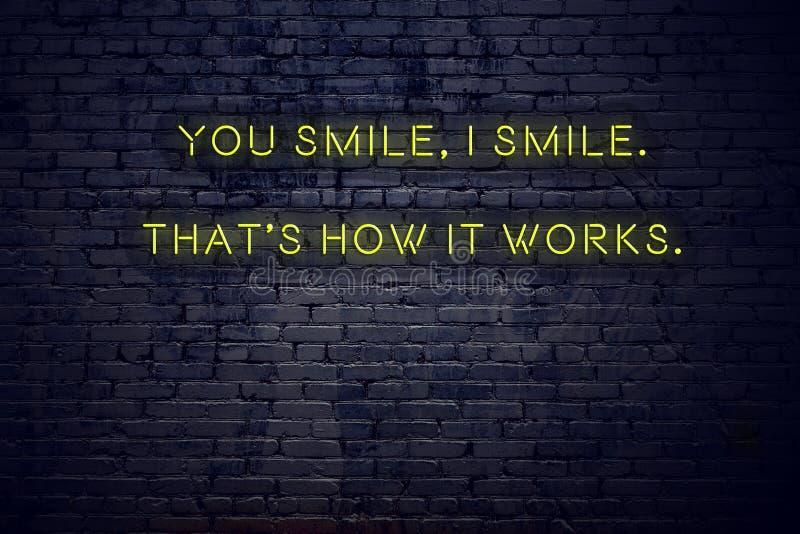 Positives Anspornungszitat auf Leuchtreklame gegen Backsteinmauer lächeln Sie ich lächeln, der ist, wie es funktioniert lizenzfreie abbildung