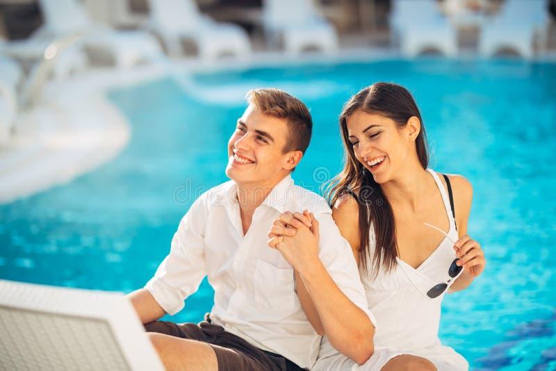 Positives glückliches Paar, das durch den Swimmingpool im Luxussommerferienort sich entspannt Zeit in der Badekurort Wellnessmitt stockbild