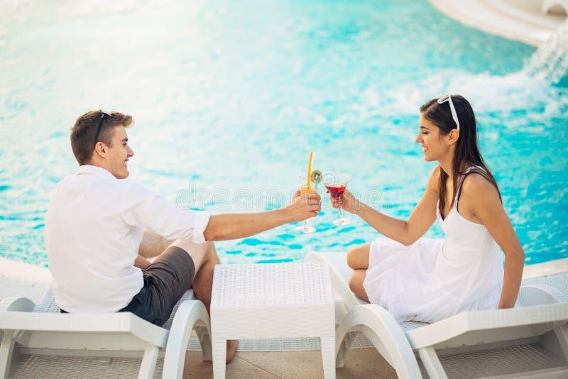 Positives glückliches Paar, das einen romantischen Nachmittag durch das Pool im Luxussommerferienort hat Trinkende Cocktails Ents lizenzfreies stockbild