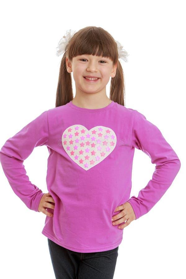 Positives kleines Mädchen, das mit den Armen in die Seite gestemmt steht lizenzfreies stockbild