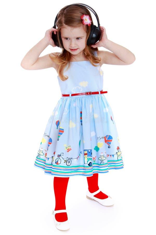 Positives kleines Mädchen, das Musik mit großem hört lizenzfreie stockfotos