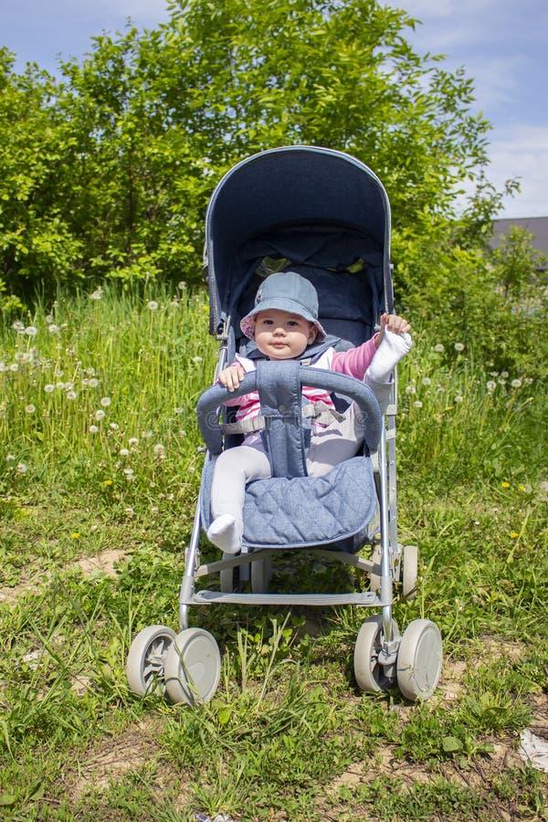 Positives kleines Mädchen in einem Spaziergänger, der mit ihren Beinen auf einem Weg spielt Sonniger Tagesbaby tritt Füße auf Nat stockbild