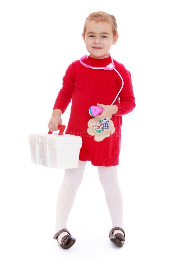 Positives kleines Mädchen mit einer Ausrüstung der ersten Hilfe in stockbilder