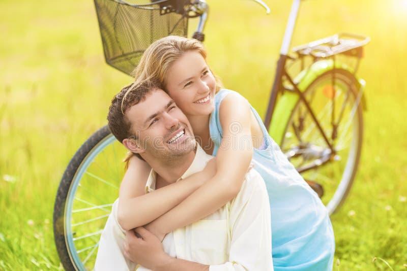 Positives lächelndes glückliches Paar, das zusammen draußen mit Bik sitzt stockfotografie
