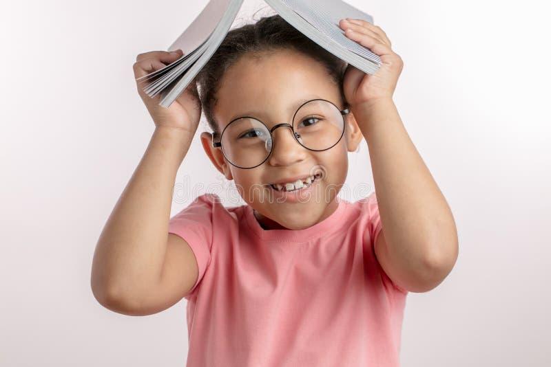 Positives Mulattemädchen hat Spaß mit einem Buch lizenzfreies stockfoto