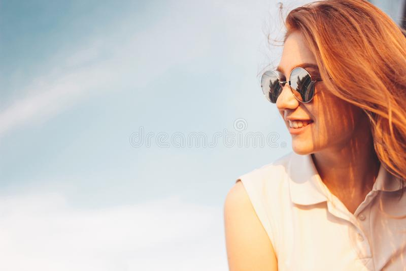 Positives sch?nes gl?ckliches rotes behaartes M?dchen in der Spiegelsonnenbrille auf Hintergrund des blauen Himmels, Sommersonnen stockfotos