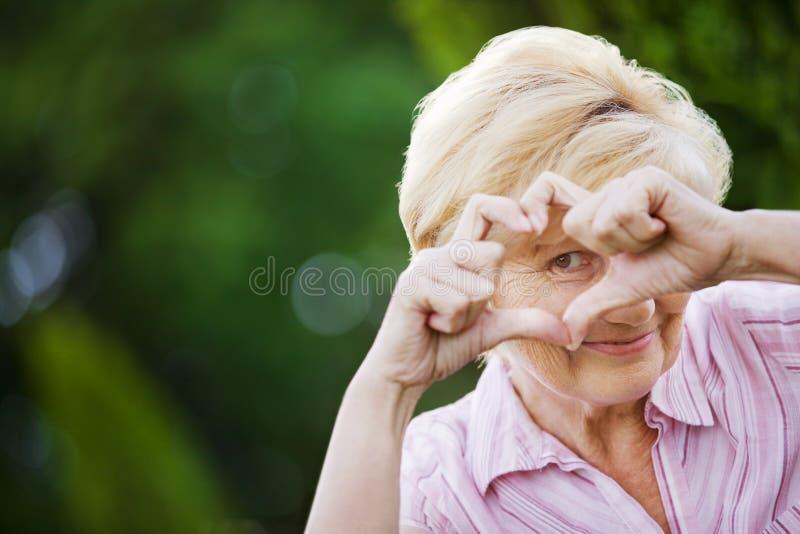 Positividade. Mulher superior engraçada feliz que mostra o símbolo do coração imagens de stock