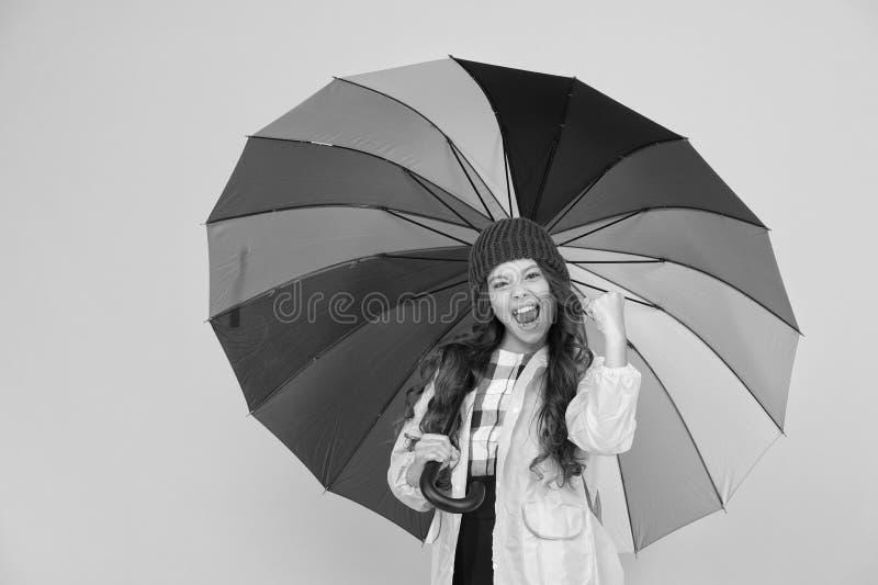 Positivity concept. Rainy day fun. Happy walk under umbrella. Enjoy rain concept. Kid girl happy hold colorful rainbow. Umbrella. Rainy weather with proper royalty free stock images