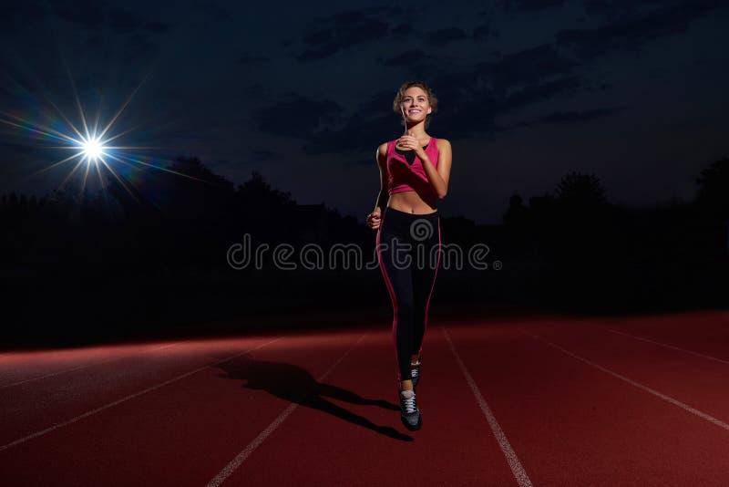 Positivity kobiety działający szkolenie na stadium przy nighttime obraz royalty free