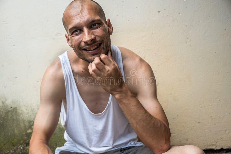 Positivo calvo anoréxico magro novo e homem desabrigado de sorriso feliz que sentam-se na rua urbana na cidade ou na cidade perto fotos de stock